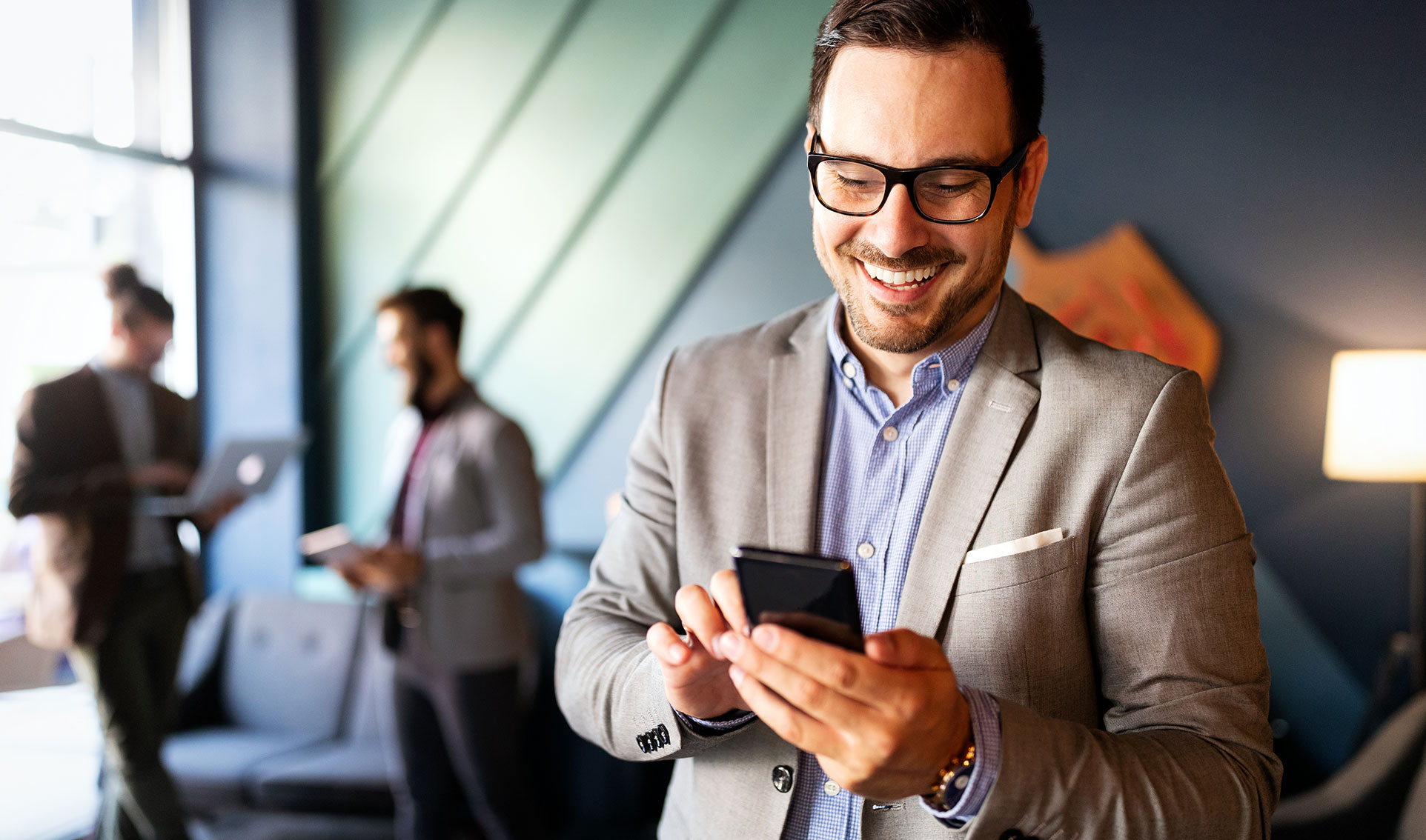 Man smiling as he looks at phone